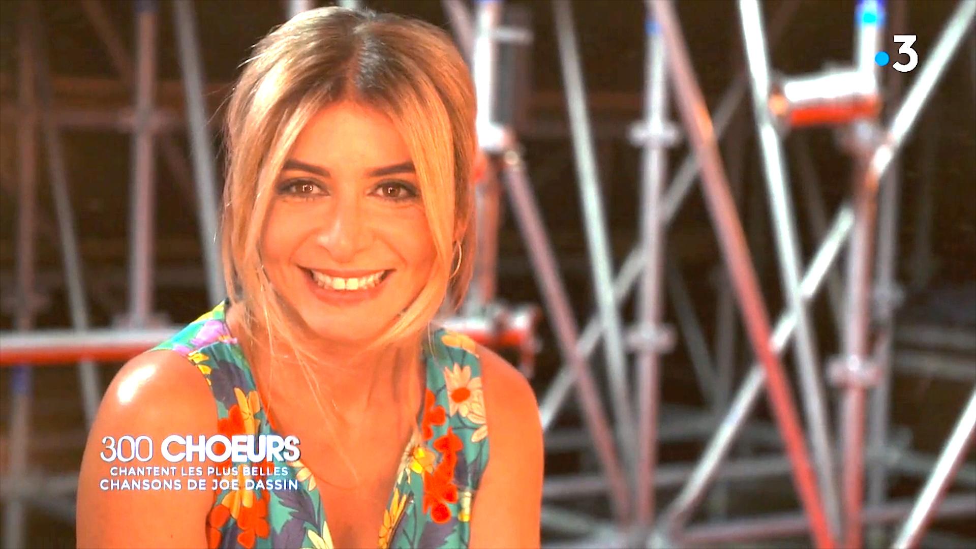 """Julie sourie à l'image sur le plateau des """"300 choeurs""""."""